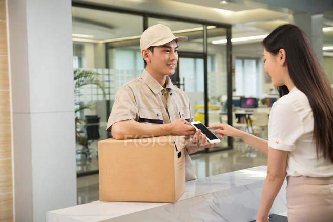 Sonriente joven repartidor con caja de cartón en empresaria con smartphone en oficina - foto de stock