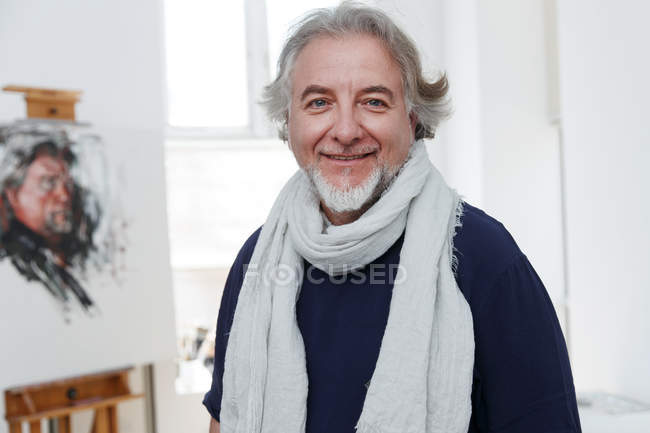 Portrait of handsome happy male artist smiling at camera in studio — Stock Photo