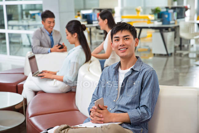 Handsome young asian businessman holding smartphone and smiling at camera in office — Stock Photo