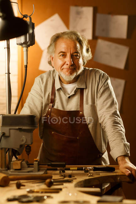 Professional mature jewelry designer in apron leaning at table with tools and smiling at camera in workshop — Foto stock
