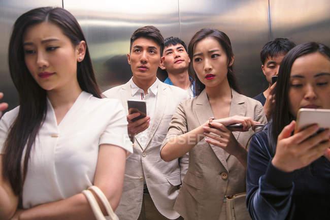 Occupato giovani asiatici utilizzando smartphone in ascensore — Foto stock