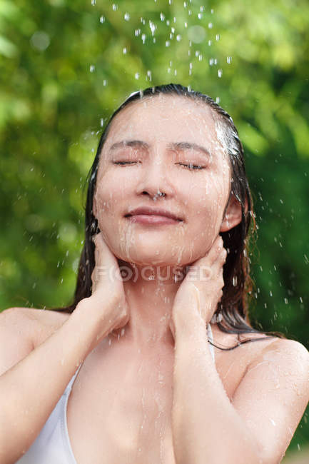 Close-up view of beautiful young asian woman taking shower with closed eyes — Stock Photo