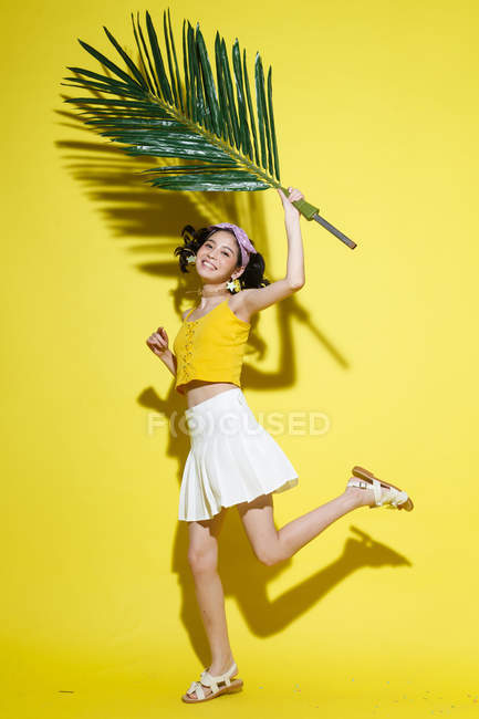 Full length view of beautiful happy asian girl holding green palm leaf and smiling at camera on yellow background — Stock Photo