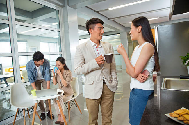 Smiling young business colleagues holding cups and talking during coffee break in office — Stock Photo