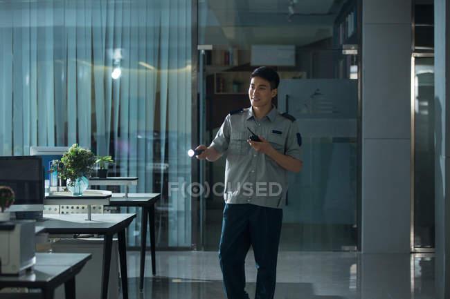 Молодой азиатских охранник проведения фонарик и с помощью рации в офисе в ночное время — стоковое фото