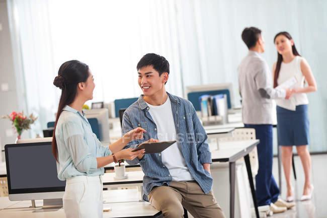 Souriant jeunes asiatiques collègues d'affaires en utilisant tablette numérique et de discuter du travail au bureau — Photo de stock