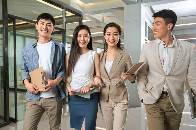 Professional young asian businessmen and businesswomen smiling at camera while walking together in office — Stock Photo