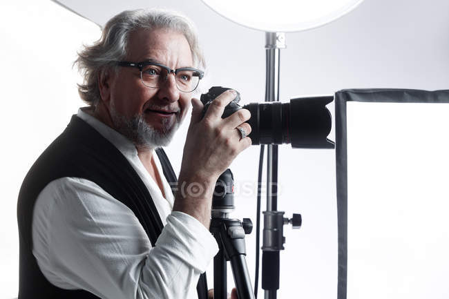 Professional smiling mature photographer working with photo camera and looking away in studio — Stock Photo