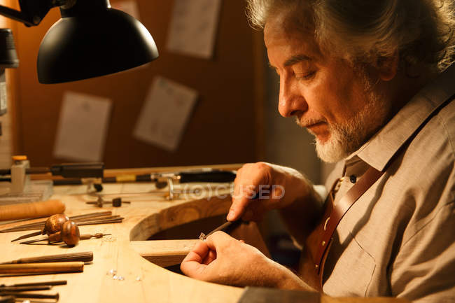 Side view of focused mature jewelry designer working with tools in workshop — Stock Photo