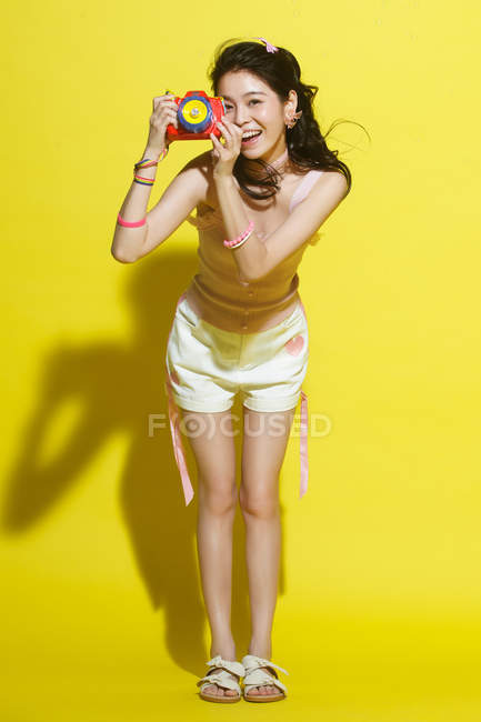 Full length view of beautiful young woman holding colorful camera and smiling on yellow background — Stock Photo