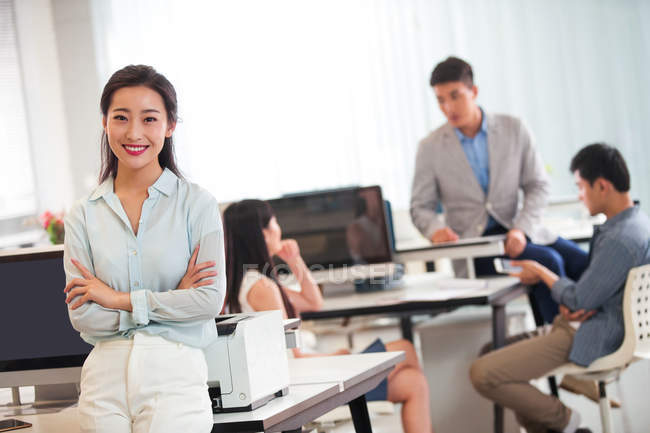 Confident asian businesswoman with crossed arms smiling at camera while colleagues working behind in office — Stock Photo