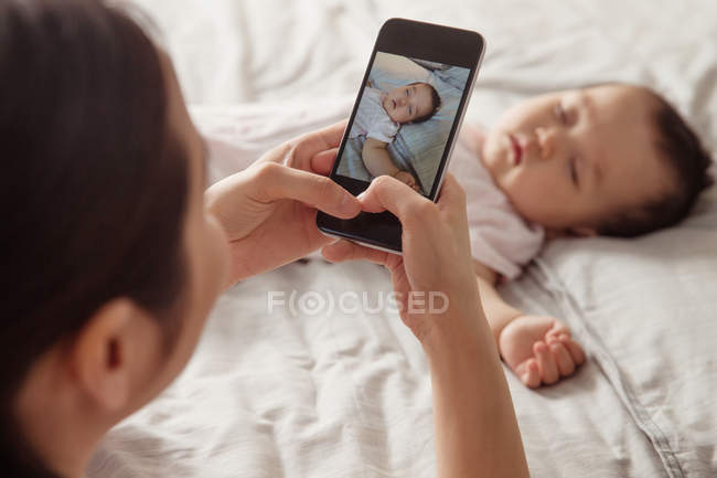 Cropped shot of young mother holding smartphone and photographing adorable baby sleeping on bed — Stock Photo
