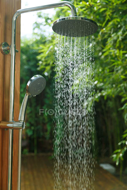 Close-up view of shower with falling water and green natural background — Stock Photo
