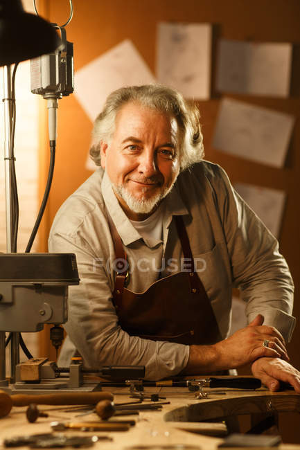 Professional happy mature jewelry designer in apron leaning at table with tools and smiling at camera in workshop — Foto stock
