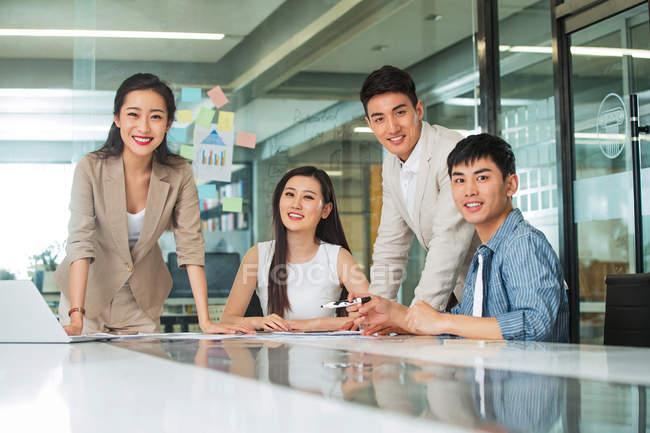 Професійні молоді азіатські бізнесмени та бізнес-жінки посміхаються на камеру під час роботи разом в офісі — стокове фото