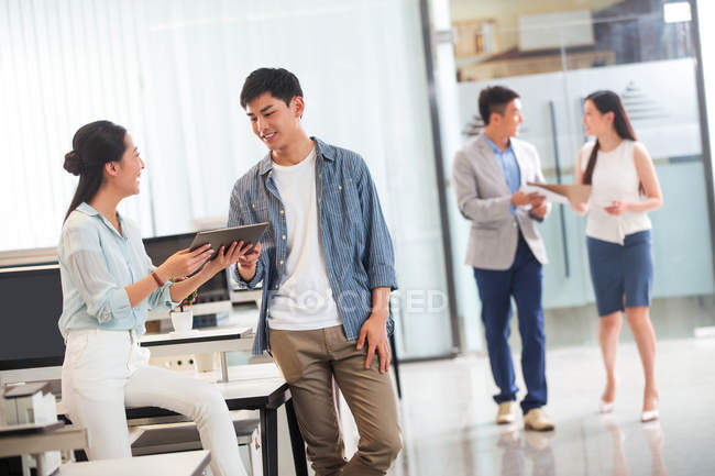 Smiling asian businessman and businesswoman using digital tablet while colleagues talking behind in office — Stock Photo