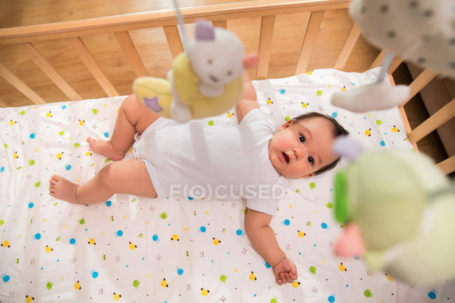 Top view of adorable asian baby lying in crib and looking at camera, selective focus — Stock Photo