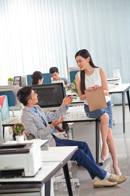 Beautiful young asian businesswoman holding clipboard and talking with male colleague in modern office — Stock Photo