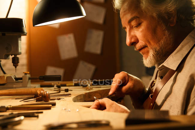 Side view of focused mature male jewelry designer working with tools in workshop — Stock Photo