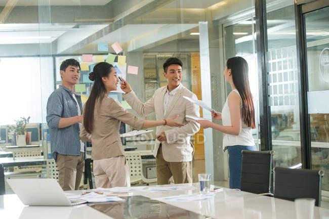 Молодые профессиональные азиатские предприниматели, работающие с липкими нотами в офисе — стоковое фото