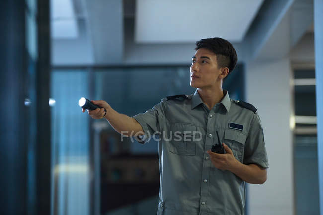 Young asian security guard holding walkie-talkie and flashlight at night — Stock Photo