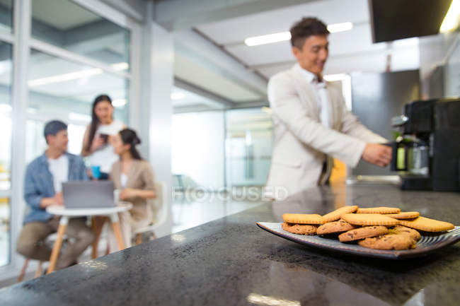 Close-up view of cookies on plate, man making coffee and coworkers using laptop during break in office — Stock Photo