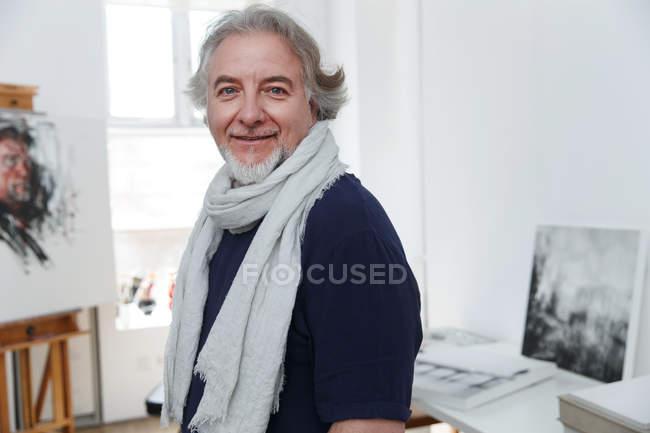 Portrait de heureux artiste masculin souriant à la caméra en studio — Photo de stock
