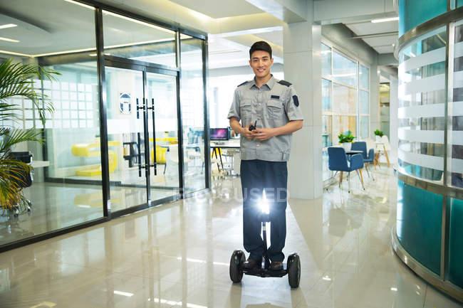 Улыбающийся молодой охранник езда самобалансирующееся скутер и использовать рацию в бизнес-центре — стоковое фото