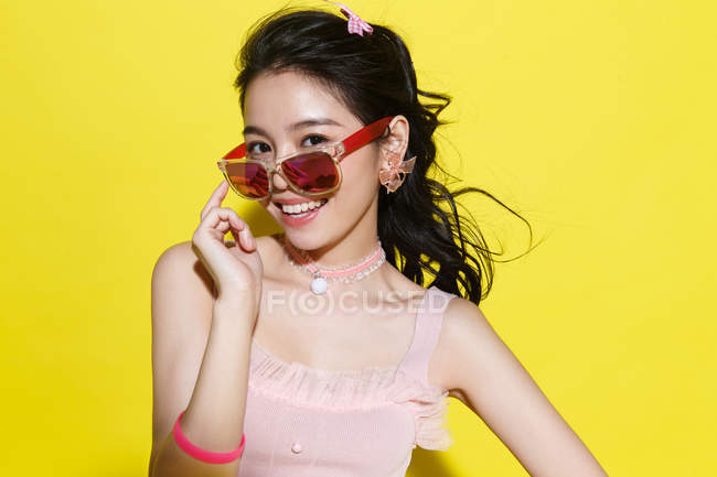Beautiful happy young asian woman adjusting sunglasses and smiling at camera on yellow background — Stock Photo