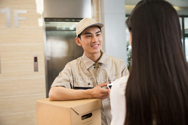 Smiling young courier with package looking at businesswoman using smartphone in office — Stock Photo
