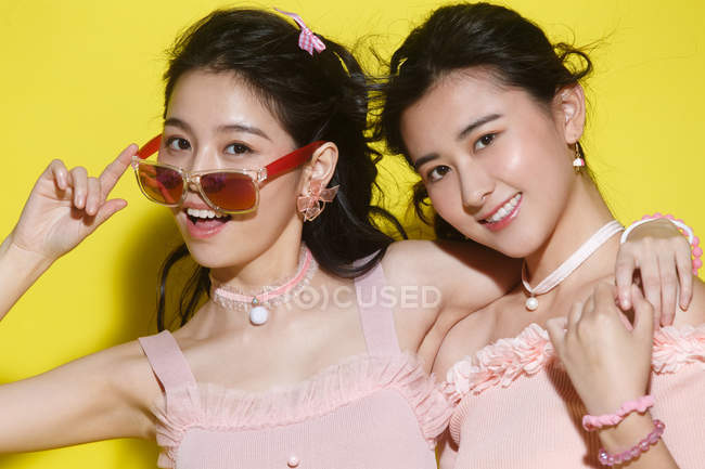 Beautiful stylish young women posing together and smiling at camera on yellow — Stock Photo