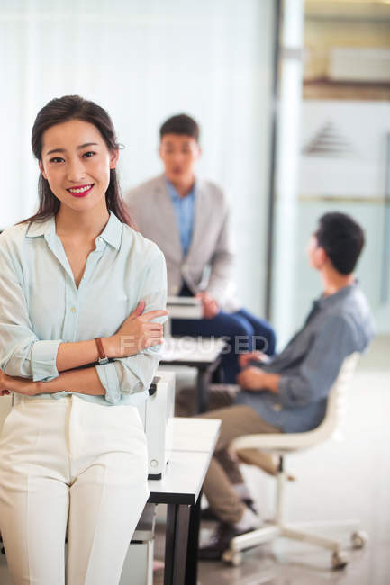 Confident young asian businesswoman with crossed arms smiling at camera in office — Stock Photo