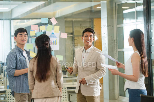 Professional young businessmen and businesswomen working together and discussing project in modern office — Stock Photo