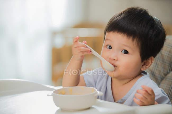 Schönes Kleinkind isst mit Löffel und schaut zu Hause in die Kamera — Stockfoto