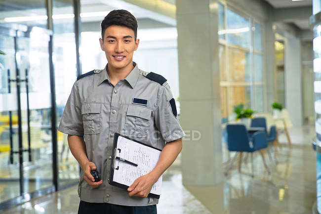 Smiling young asian security guard holding walkie-talkie and clipboard — Stock Photo