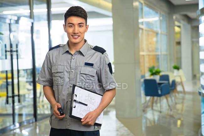 Lächelnder junger asiatischer Wachmann mit Walkie-Talkie und Klemmbrett — Stockfoto