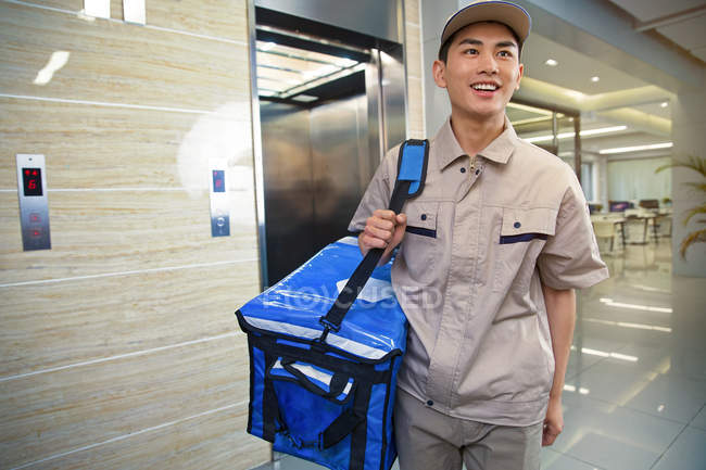 Sorrindo jovem asiático entrega homem com saco olhando para longe no centro de negócios — Fotografia de Stock