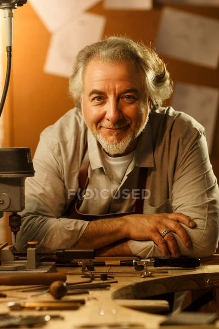 Professional mature male jewelry designer sitting at workplace and smiling at camera — Foto stock