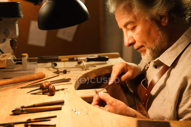 Profile view of focused mature male jewelry designer working with tools in workshop — Foto stock