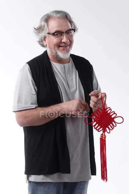 Мужчина средних лет, держащий красный китайский узел и улыбающийся в камеру, изолированную на сером — стоковое фото