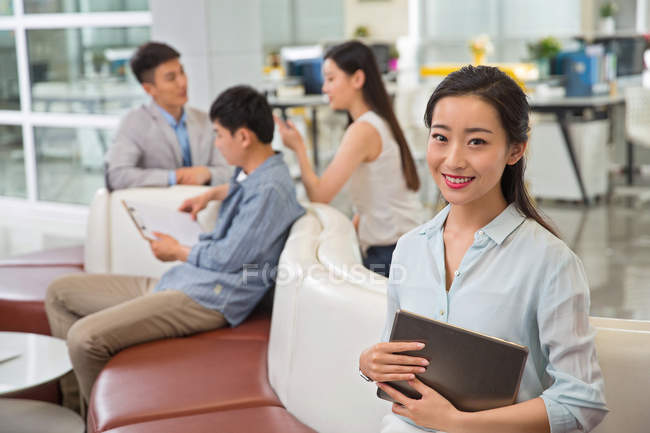 Attractive young asian businesswoman holding digital tablet and smiling at camera in office — Stock Photo