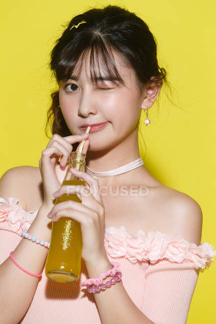 Beautiful young woman drinking refreshing beverage and winking at camera on yellow — Stock Photo