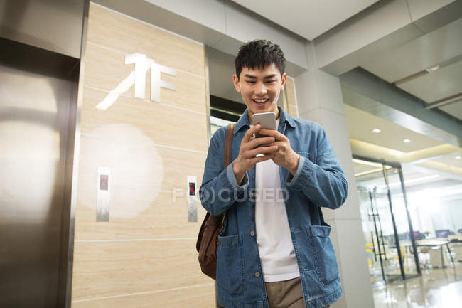 Low angle view of smiling young asian businessman using smartphone near elevator in office — Stock Photo