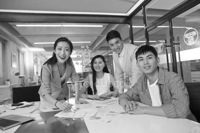 Black and white image of young asian business team working together and smiling at camera in office — Stock Photo