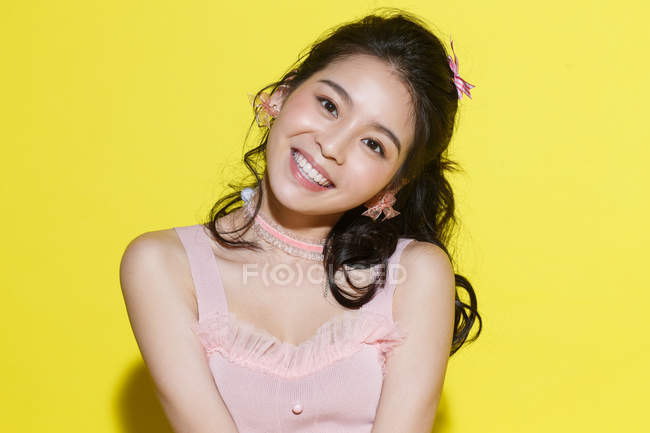 Portrait of beautiful happy young asian woman smiling at camera on yellow background — Stock Photo