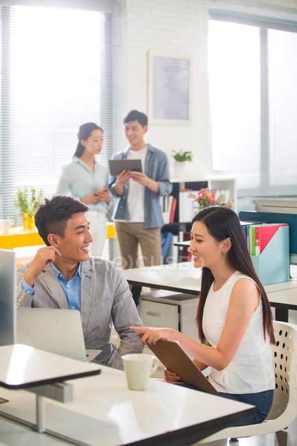Sorridenti giovani colleghi di sesso maschile e femminile che parlano mentre lavorano insieme in ufficio — Foto stock