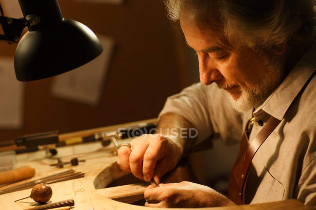 Close-up view of concentrated mature jewelry designer working with tools in workshop — Stock Photo