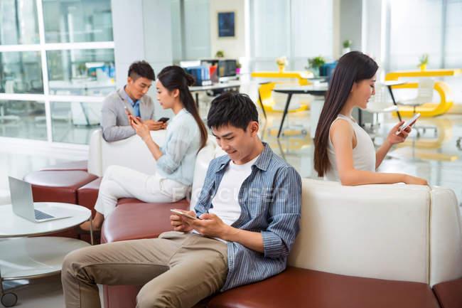 Young asian people sitting and using smartphones in modern office — Stock Photo