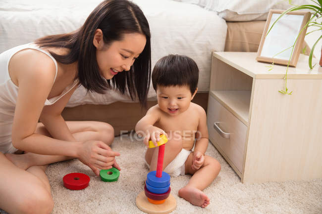 Happy young mother looking at baby playing with colorful educational toy at home — Stock Photo