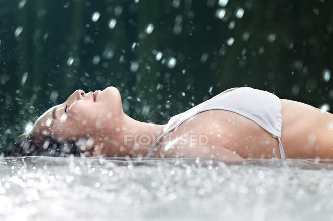 Vista laterale di sorridente giovane donna in Bikini sdraiato in Spa e godendo doccia — Foto stock